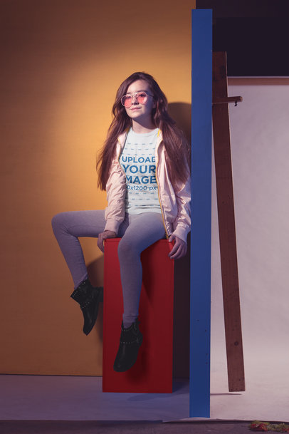 Cool Little Girl Wearing a T-Shirt Mockup Sitting on a Colored Structure a19588