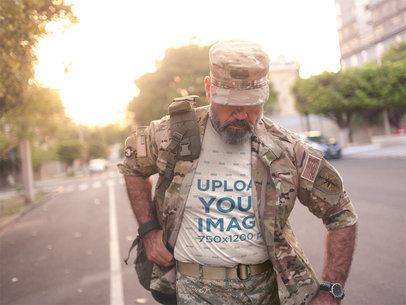 Veteran in Uniform Wearing a T-Shirt Mockup Walking Down the Street a20634