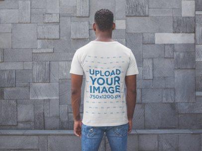 Back Shot T-Shirt Mockup of a Man Facing a Modern Stone Wall 20744