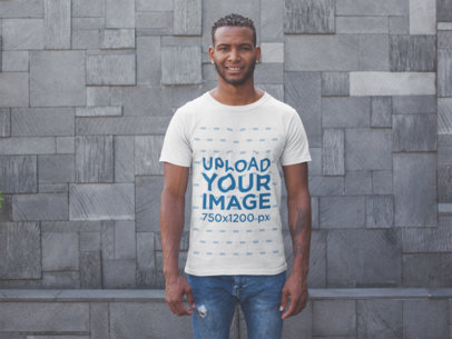 Mockup of a Smiling Man Wearing a Tshirt Standing Against a Modern Stone Wall 20744