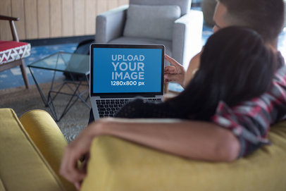 MacBook Mockup Being Used by a Couple Relaxing on a Couch a20770