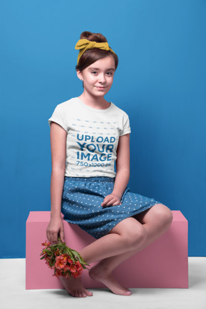 Smiling Girl Wearing a T-Shirt Mockup Holding a Flowers Bouquet while Sitting a19584