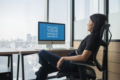 iMac Mockup Featuring a Young Woman by Her Desk at a Corporate Office a20759