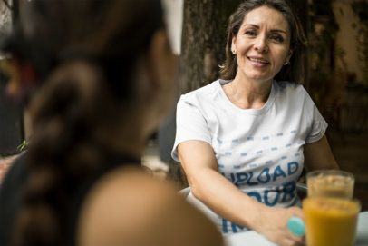 Senior Lady Wearing a Tshirt Mockup while Chatting at a Cafe a20361