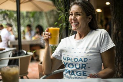 Happy Senior Lady Drinking an Orange Juice Wearing a T-Shirt Mockup a20362