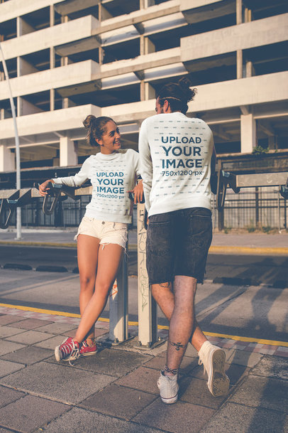 Portrait of a Couple Wearing Crewneck Sweaters Mockup Outside a Big Building a20591
