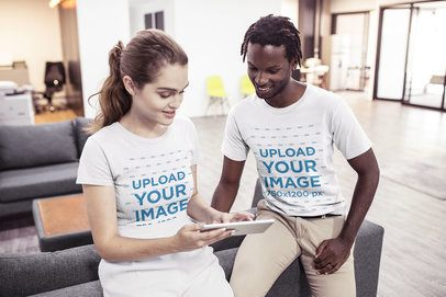 Interracial Pair of Coworkers Wearing T-Shirts Mockup While Discussing a Task a20521