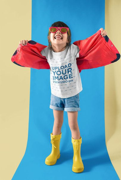 Little Girl Playing with her Red Jacket Wearing a Tshirt Mockup in a Two Colors Room a19473