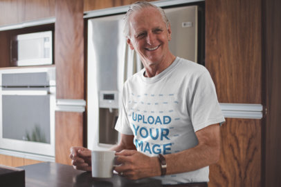 Smiling Senior Man Having a Cup of Coffee Wearing a T-Shirt Mockup a20484