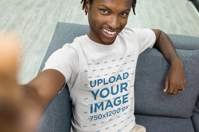 Selfie of a Black Man with Short Dreadlocks Wearing a T-Shirt Mockup Sitting on a Sofa a20533