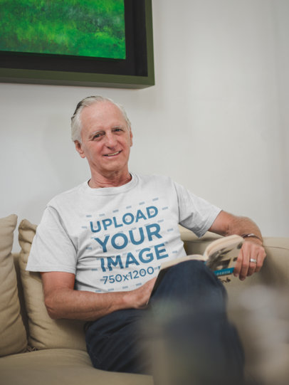 Senior Man Wearing a T-Shirt Mockup Reading a Book Sitting on the Sofa a20504