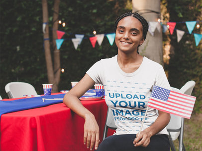 Smiling Black Woman Wearing a Tshirt Mockup Holding a Small American Flag at a 4th of July BBQ Party a20829