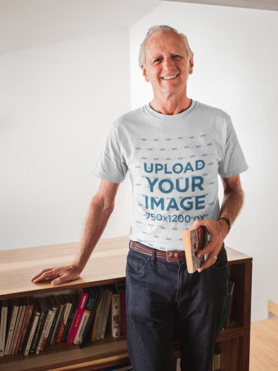Smiling Man Wearing a Tshirt Mockup Holding a Book in his House a20506
