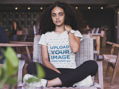 Black Woman Wearing a Tshirt Mockup Sitting on a Wooden Chair a20417