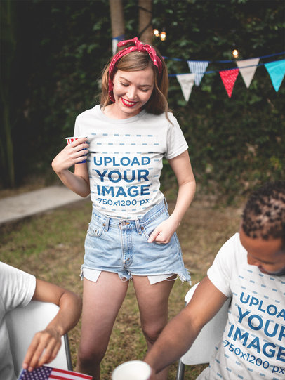 Smiling Blonde Girl and her Friend Wearing a Tshirt Mockup at a 4th of July BBQ Party a20821