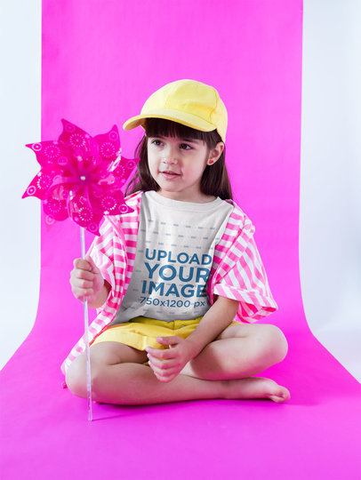 Little Girl Wearing a Round Neck Tee Mockup Holding a Pinwheel a19467