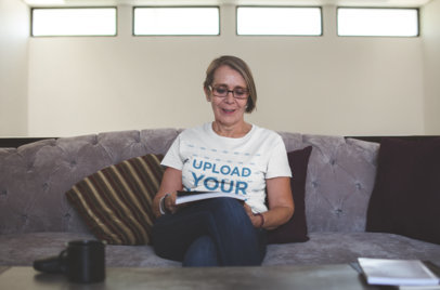 Senior Woman Wearing a Tshirt Mockup Sittng on a Sofa while Reading a20671