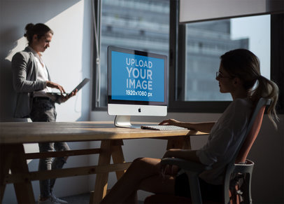 Girl Working with an iMac Mockup Near the Window with her Coworker a20977