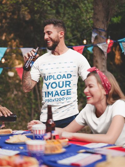 Tattooed Man Wearing a Tshirt Mockup Drinking a Beer at a 4th of July BBQ Party a20832