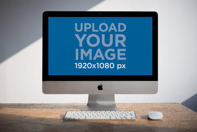 iMac Mockup Standing on a Wooden Desk Against a Diagonal Ray of Sun Light a20980