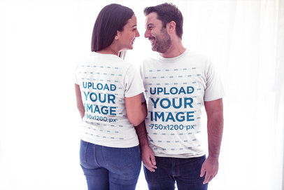 Mockup of a Couple Wearing T-Shirts Aganist White Curtains a20608