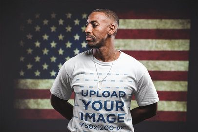 Man Wearing a Tshirt Mockup Standing Against an American Flag a20924