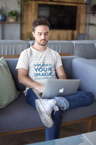 Serious White Man Wearing a T-Shirt Mockup Working with his Laptop on a Sofa a20437