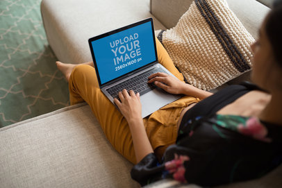 MacBook Mockup of a Woman Working while Sitting on a Sofa a21166