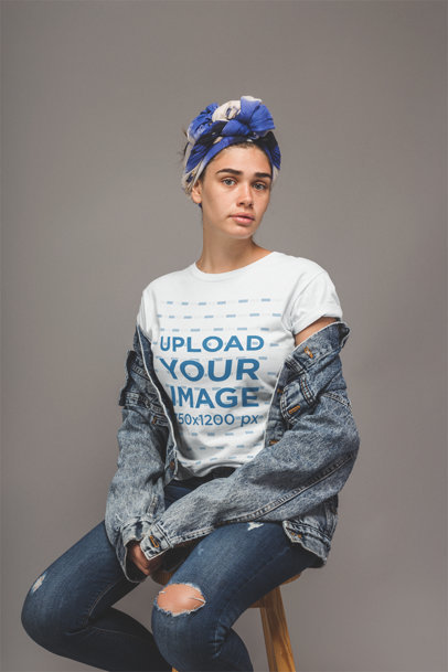 Freckled Woman with Denim Clothing Wearing a T-Shirt Mockup Sitting on a Stool a20887