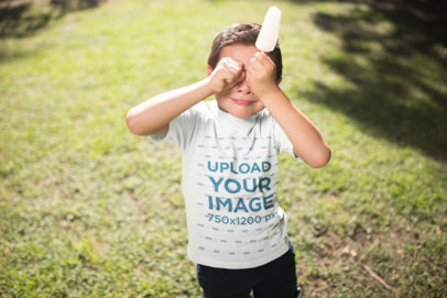 Mockup of a Kid with a Popsicle Wearing a T-Shirt Outdoors a20956