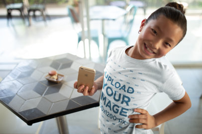Mockup of a Child Posing with her Phone while Wearing a T-Shirt a20966