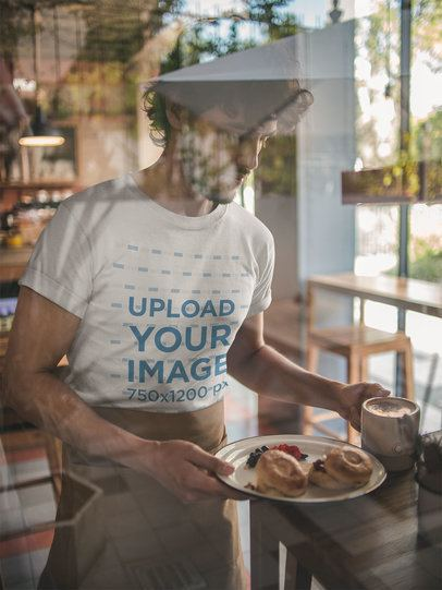 Behind a Window T-Shirt Mockup of a Waiter Wearing a Waist Apron while Serving Breakfast a20482