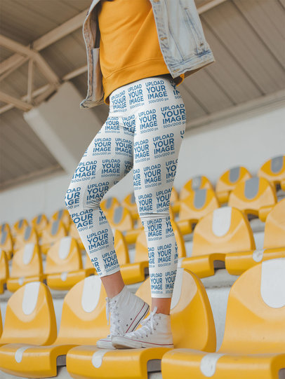Leggings Mockup of a Woman Standing on Yellow Stadium Seats a19040
