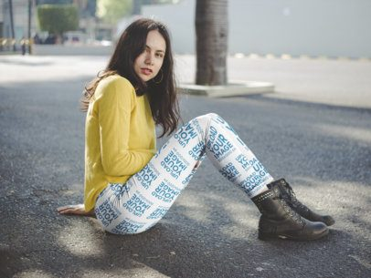 Side Shot Mockup of a Woman Sitting on the Street Wearing Leggings and a Yellow Sweater a19062