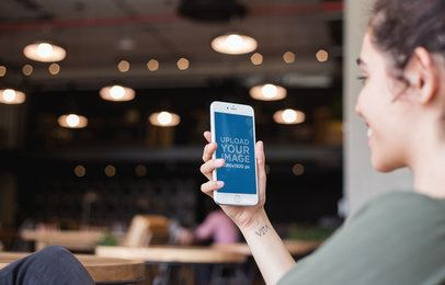 Silver iPhone 8 Mockup Featuring a Happy Woman with a Wrist Tattoo at a Restaurant a21267