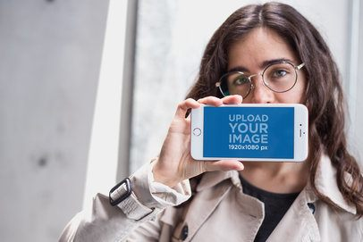 Mockup of a Girl Holding a Rose Gold iPhone 7 Plus in Landscape Position Against her Mouth a21277