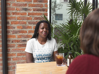 Mockup of a Black Woman Wearing a T-Shirt with a Friend at a Cafe a21405