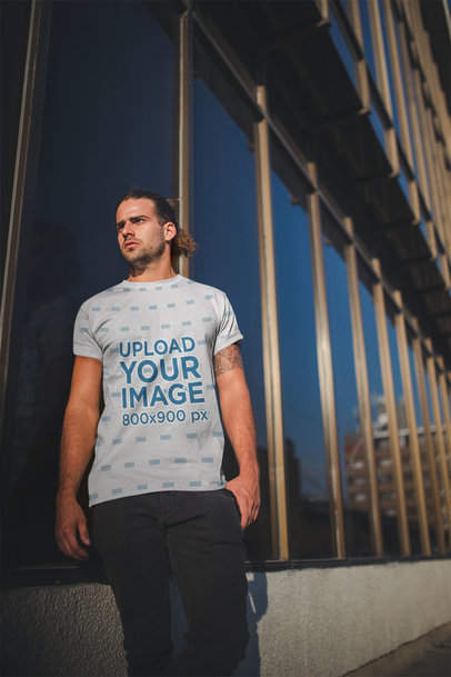Mockup of a Man Wearing a Sublimated Tshirt Against a Building's Mirrors a19939