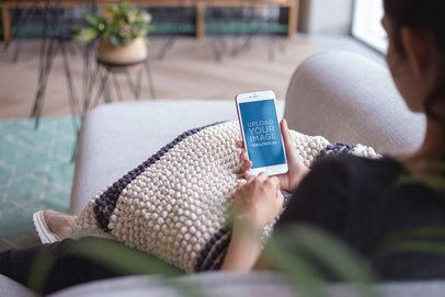 Mockup of a Woman Using a Rose Gold iPhone Sitting on a Sofa a21283