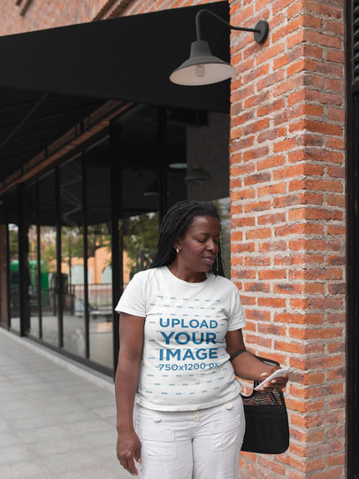 T-Shirt Mockup of a Black Lady Walking Down the Street Checking her Smartphone a21407