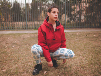 Mockup of a Girl Wearing Leggings and a Red Hooded Coat while Crouching at a Park a19190