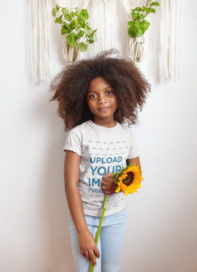 Mockup of a Little Girl Wearing a T-Shirt Holding a Sunflower a21318