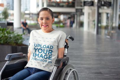 Mockup of a Girl Using a Wheelchair and Wearing a T-Shirt Outside a Mall a21356