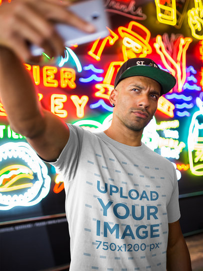 T-Shirt Mockup of a Black Man Taking a Selfie Against Neon Signs a18307
