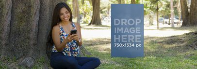 Young Girl Using Her Black iPhone 6 Under a Tree