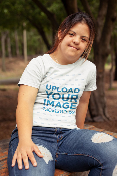 Mockup of a Girl Wearing a T-Shirt Sitting on a Bench at a Park a21387