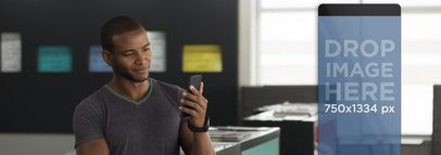 Mockup of Young Man Using his Smartphone at a Creative Office