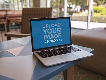 Mockup Featuring a MacBook Standing on the Border of a Small Table a21509