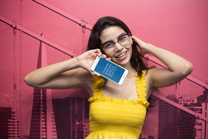 Mockup of a Happy Woman Holding an iPhone Against a Pink Printed Wall a21448