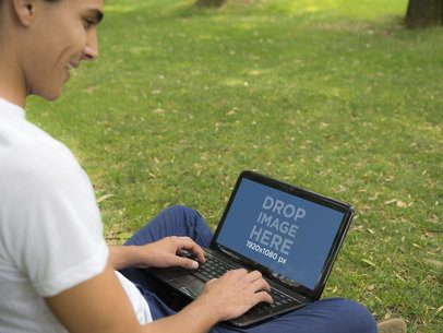 Young Man Sitting on Grass in Park and Using an HP Laptop